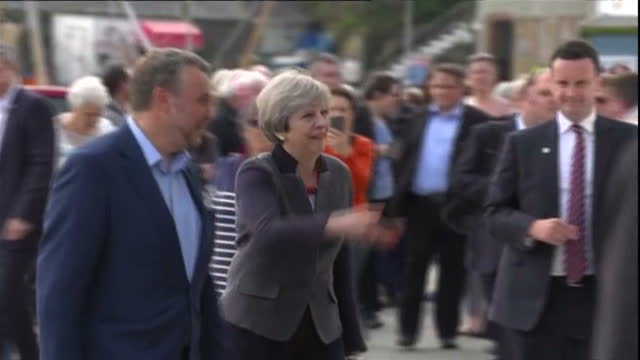external shots prime minister theresa may visits port in helston talks to workers smiling and laughing in helston walks by seaside in helston england... - cornovaglia video stock e b–roll