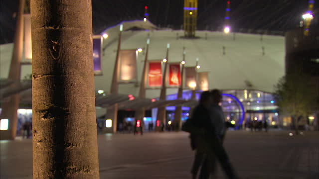 external showing greenwich o2 area at night, people walk under decorative bridge to large concert venue in london on july 02, 2014 in greenwich,... - モンティ・パイソン点の映像素材/bロール