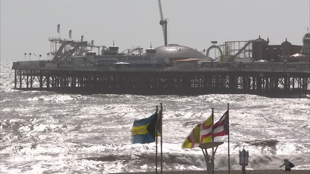 external wide shots of brighton pier with strong winds causing waves on sea in foreground brighton seafront stockshots on april 18, 2013 in brighton,... - ブライトン パレスピア点の映像素材/bロール
