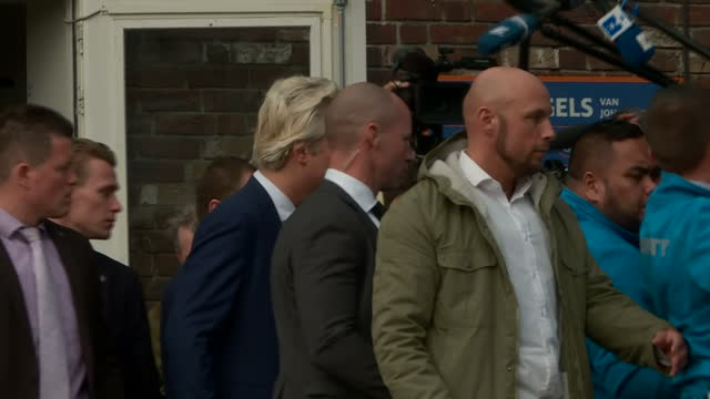 external wide side shot geert wilders founder and leader of the party for freedom in netherlands walking out after voting in the netherlands... - オランダ点の映像素材/bロール