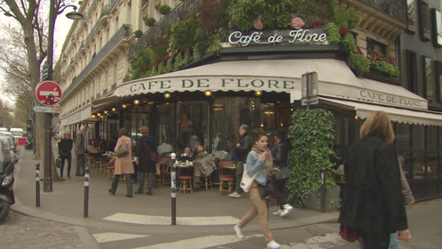 externals of café de flore paris close up of signage and flower boxes above the sign entrance to the café seen from across road with traffic passing... - pampering stock videos & royalty-free footage