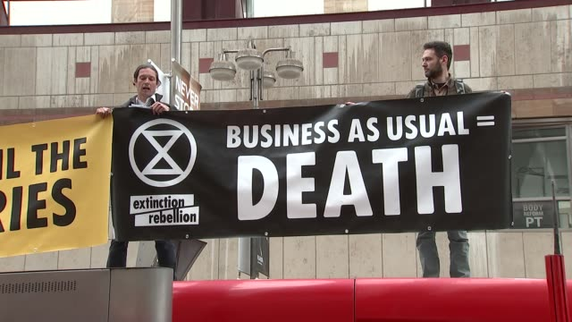 extinction rebellion activists protests atop dlr train at canary wharf; uk, london: extinction rebellion climate change activists protest atop dlr... - protestor stock videos & royalty-free footage