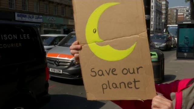 Extinction Rebellion climate change protesters block roads in London ENGLAND London EXT Vox pop SOT Sign 'Sorry but this is important' Protester...