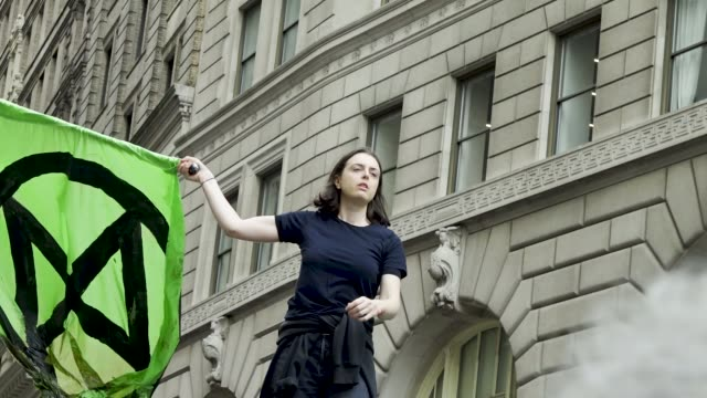 extinction rebellion environmental activist pour fake blood atop of the wall street charging bull statue in the financial district of downtown... - climate finance stock videos & royalty-free footage