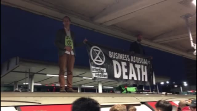 extinction rebellion protester dragged from train by commuters at canning town; england: london: canning town: ext / early morning amateur video... - protestor stock videos & royalty-free footage