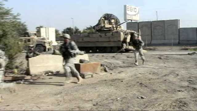 extra us troops in baghdad armed us soldiers from back of armoured vehicle answering call for help from iraqi army and soldiers climbing stairs to... - バグダッド点の映像素材/bロール