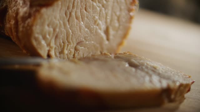 extreme close up a juicy breast of grilled white chicken is sliced with a sharp knife on a wooden cutting board as part of a recipe preparation in slow motion. - sandwich stock videos & royalty-free footage