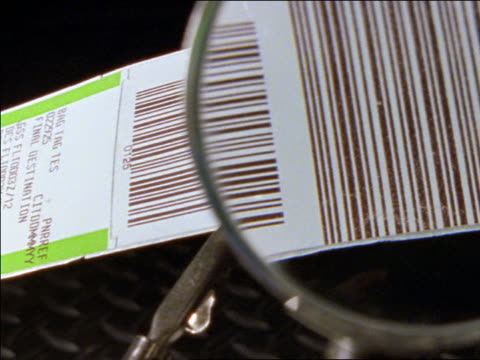 extreme close up PAN baggage claim check bar code under magnifying glass