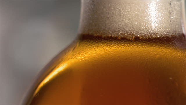extreme close up beer bottle with tiny bubbles gathering in foam at neck / london - 2005 stock videos & royalty-free footage