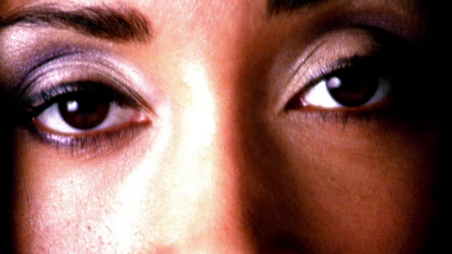 HIGH CONTRAST extreme close up brown eyes of young Black woman looking at camera then looking to side in studio