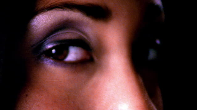 high contrast extreme close up brown eyes of young black woman turning to camera then away in studio / rack focus - high contrast stock videos & royalty-free footage