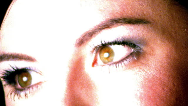 high contrast overexposed extreme close up brown eyes of young woman looking away then toward camera in studio - high contrast stock videos & royalty-free footage