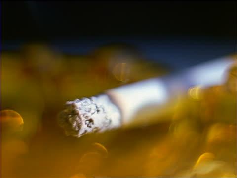 extreme close up burning cigarette resting on ashtray