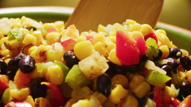 extreme close up camera moves across a bowl of mexican corn salsa with black beans tomato and green pepper. - 野菜 とうもろこし点の映像素材/bロール