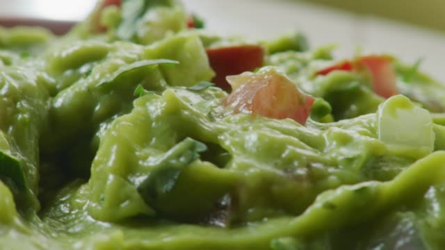 extreme close up camera moves over a bowl of freshly made guacamole with tomatoes onion and cilantro. - dipping stock videos & royalty-free footage