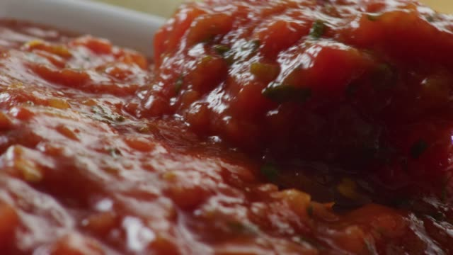 vidéos et rushes de extreme close up camera moves over a bowl of freshly made taco sauce or salsa with tomato pepper and spices. - tomate