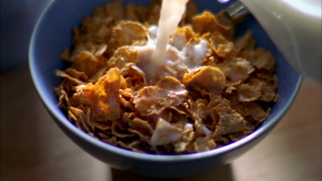 extreme close up cereal in blue bowl w/spoon / milk pouring into cereal from bottle - breakfast cereal stock videos & royalty-free footage