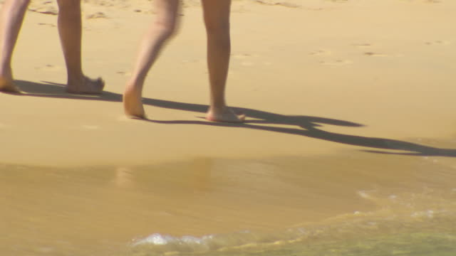 extreme close up clear shallow harbour water on sandy base pan to gentle waves breaking on beach / anonymous bare feet and legs walking on sand /...
