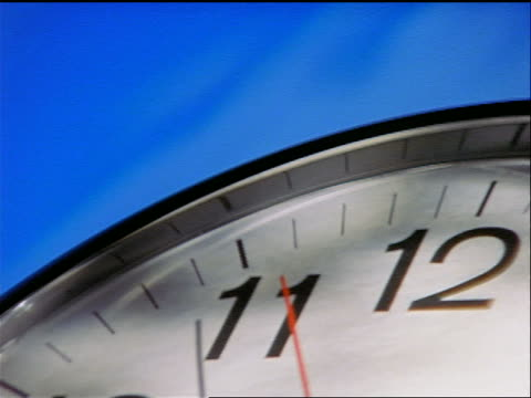 extreme close up pan distorted wall clock with blue background - inquadratura dall'alto di un tavolo video stock e b–roll