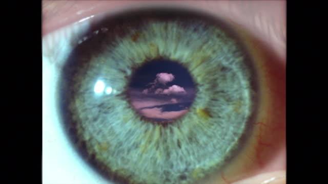 vídeos de stock e filmes b-roll de extreme close up eye blinking with time lapse clouds in pupil - filme colagem