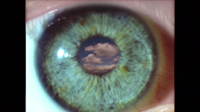 extreme close up eye blinking with time lapse clouds in pupil - blinzeln stock-videos und b-roll-filmmaterial