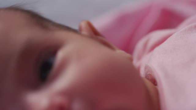 Extreme close up eye, ear and nose of a tiny baby as she lays in her crib.