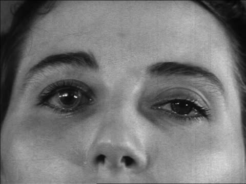 stockvideo's en b-roll-footage met b/w 1936 extreme close up eyes of woman wearing early contact lens / newsreel - oogmeetkunde