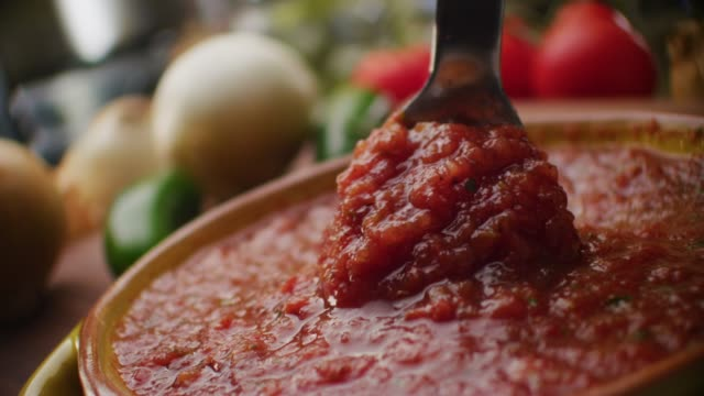 extreme close up featuring a beautiful bowl of freshly prepared taco sauce surrounded by ingredients such as onions peppers and tomatoes. - rühren stock-videos und b-roll-filmmaterial