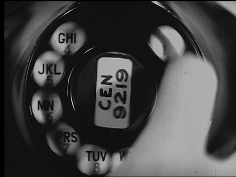 B/W extreme close up finger dialing rotary telephone