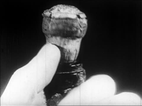 b/w 1928 extreme close up fingers of man popping cork on champagne bottle / newsreel - champagne stock videos & royalty-free footage