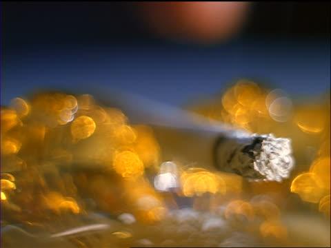 extreme close up fingers picking up burning cigarette from ashtray