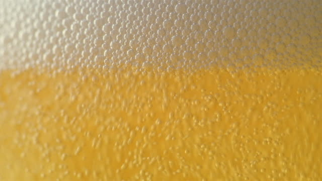 extreme close up foam rising as beer is poured into glass - 飲み物の泡点の映像素材/bロール