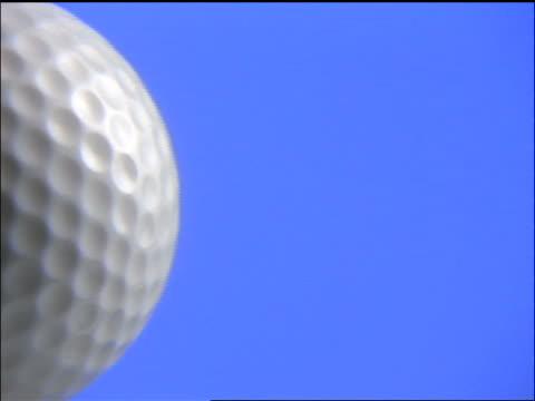 vídeos de stock e filmes b-roll de extreme close up golf ball spinning past camera with blue background - extreme close up