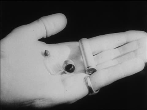 B/W 1945 extreme close up hand holding cyanide capsule Heinrich Himmler used to kill himself / newsreel