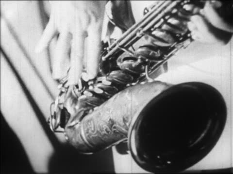 B/W 1928 extreme close up hands of man playing saxophone quickly / newsreel