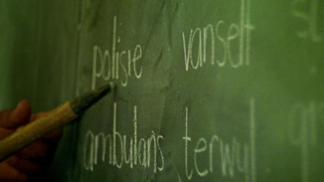 vidéos et rushes de extreme close up hands of teacher pointing to words in afrikaans on chalkboard in classroom / south africa - enseigner