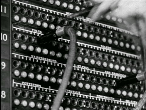 b/w 1946 extreme close up hands of telephone operator plugging in wires at switchboard / industrial - switchboard operator stock videos & royalty-free footage