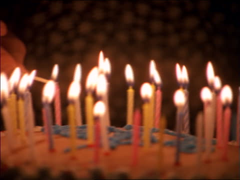extreme close up hands of woman lighting candles on birthday cake - compleanno video stock e b–roll