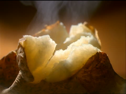 extreme close up hands opening baked potato + knife spreading butter - still life stock videos & royalty-free footage