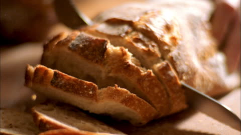 extreme close up knife slicing loaf of crusty bread - bread stock videos & royalty-free footage