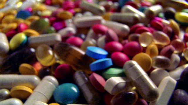 SOFT FOCUS extreme close up large amount of different colored pills rotating