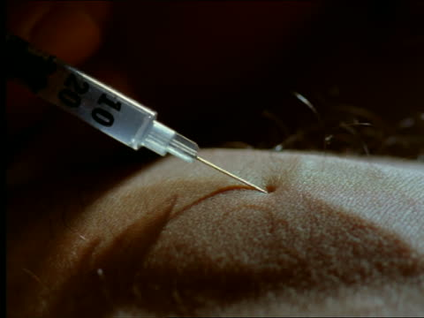 extreme close up liquid filled syringe injecting into skin