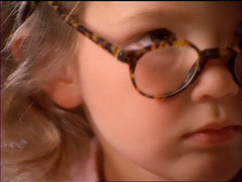 extreme close up little girl wearing glasses + taking them off - eyesight stock videos & royalty-free footage