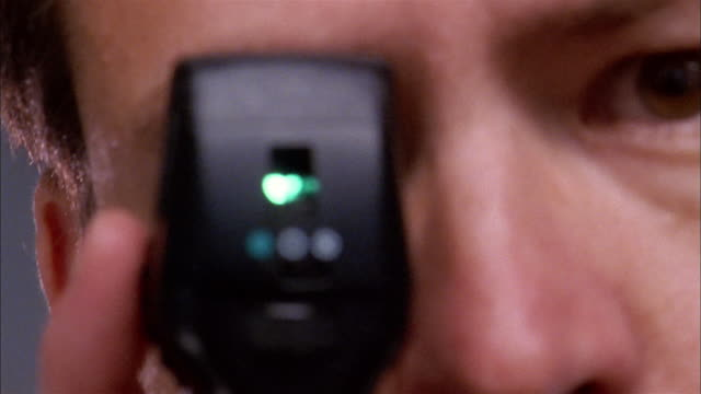 Extreme close up male eye doctor holding eye scope w/green light during eye exam and turning dial