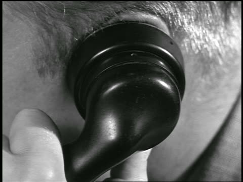 stockvideo's en b-roll-footage met b/w 1954 extreme close up man holding telephone receiver to ear / industrial - 1954