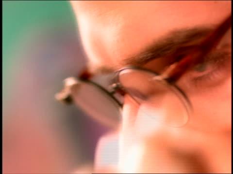 extreme close up man putting on + taking off eyeglasses / rubs eyes - dejaover点の映像素材/bロール