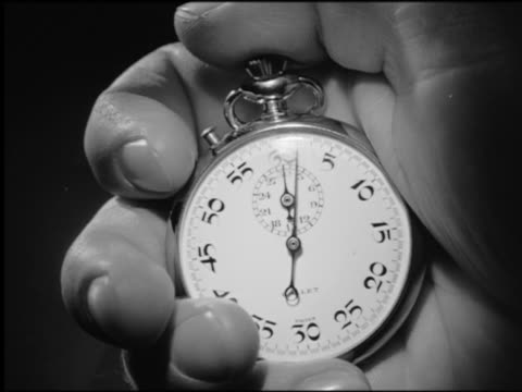 B/W extreme close up man's hand holding stopwatch + starting it with thumb