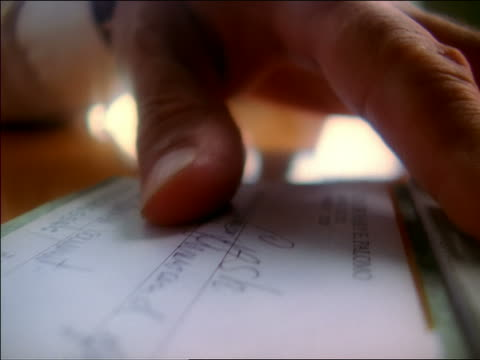 Extreme close up man's hands signing check on table and ripping it from checkbook