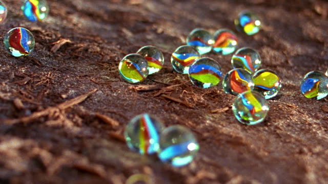 extreme close up marbles being thrown on to ground + boys' hands picking them up outdoors - marble stock videos & royalty-free footage