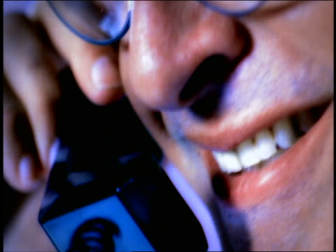 extreme close up mouth of man with eyeglasses talking on telephone nods head + smiles then shakes head + says no